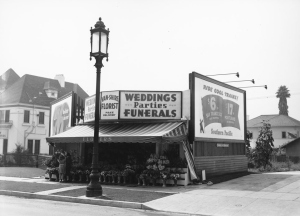 "Close-up of one of the many ""Wilshire Special"" streetlights that were prevalent along Wilshire Boulevard during the late 1920s and 1930s. The lamp post sits in front of the Van-Shire Florist open-air shop. To the left of the entrance, a young girl and woman look at the arrangements. Bilboards on either side of the shope advertise Union 76 gasoline and Southern Pacific railroad. The sign reads ""Ride cool trains! $6 to San Francisco. $17 to Portland"". (Courtesy Water and Power Associates)"