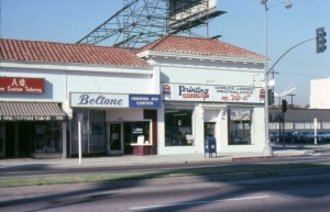 Exterior view of three storefronts located in the 5200 block of Wilshire Boulevard, just west of S. Sycamore Avenue (right). This entire Spanish style commercial building was later demolished and replaced with a fast food restaurant. Parked Cadillacs and Lou Ehler's Cadillac dealership showroom, also demolished, are partially visible on the far right. (Marlene Laskey Collection; Los Angeles Public Library)