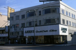 Looking south across the street towards Leed's shoe store, located at 6030 Wilshire Boulevard, and other storefronts. Photograph dated 1978. (Marlene Laskey Collection; Los Angeles Public Library)