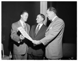A. W. Ross (center) accepting a scroll, 1951. Ross is acclaimed as the creator of the Miracle Mile. Lou Overgard, Silverwoods (left); A. W. Ross; William Mar Dell, Desmonds (right). [Los Angeles Examiner Collection; USC Digital Library]