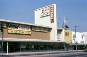 Looking northeast from across Wilshire Boulevard towards an Adray's store and other businesses located at addresses ranging from 5557-5575. Years later, the storefronts on the right occupied by Barton's Bonbonniere, Janet Shore Corsets, and Miracle Shoe Repair were remodeled to create one structure and replaced with a Smart and Final store. Adray's later became a Rite Aid pharmacy. (Marlene Laskey Collection; Los Angeles Public Library)