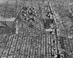 Aerial view is looking east from Fairfax with Wilshire on the right. View shows the Park La Brea Towers and Miracle Mile area. The towers, a residential community, was built at a cost of $40,000,000, which includes 18 apartment buildings 13-stories high, and business and park areas. Photo dated: February 10, 1965. (Spence Air Photos; Los Angeles Public Library)