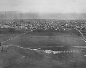 Aerial view of the Wilshire area. View shows Wilshire Boulevard at La Brea. Note oil well drilling rigs, left corner of this photo. Photograph dated 1922. (Security Pacific National Bank Collection; Los Angeles Public Library)