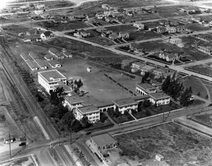 Aerial view of the Page Military Academy, located at South 1201 Cochran Avenue. In the  circa 1920s photograph Cochran runs left to right at the bottom; it intersects with San Vicente Blvd at the left (the street with the trollery track); the diagonal street on the right is Edgewood Place; and the point of the parcel is Hauser. The building at the very bottom, across from the academy, is the present location of Splendid Dry Cleaners. The academy was founded by Major Robert A. Gibbs and his wife Della P. Gibbs in 1908. The school was at this location from 1915 until 1958. (Security Pacific National Bank Collection; Los Angeles Public Library)