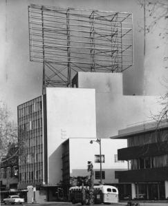 "Billboard being constructed on roof of the Hancock Oil Building, 1959. The white building in the foreground is the former Arthur Murray dance studio at Wilshire and Stanley. ""Apex Steel Corporation has completed one of the largest signposts atop a building to be erected in Los Angeles. The frame weighs more than 30 tons and is set on the Hancock Building, Wilshire Boulevard. Display area is 40 by 85 feet and was designed by Cejay Parsons, architect."" -- Examiner clipping attached to verso, dated 10 May 1959.(Los Angeles Examiner Collection, 1920-1961; USC Digital Library)"
