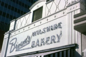 Close-up exterior view of Brown's Wilshire Bakery (1978), located at 5423 Wilshire Boulevard, showing the neon sign above the entrance. Years later, this French style storefront, the Flying Saucer restaurant to the west, and the Roman Foods Market to the east were remodeled to create one large commercial space to accommodate a Staples office supply store. (Caption and image courtesy of the Marlene Laskey Collection, Los Angeles Public Library)