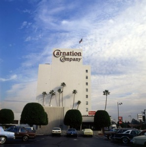 Looking east from a neighboring parking lot towards the Carnation Company 9-story office building, which contains the company headquarters and a restaurant (lower center), located at 5045 Wilshire Boulevard. Photograph dated 1980. (Carol Westwood Collection; Los Angeles Public Library)