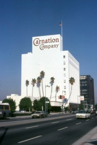 Looking northeast across Wilshire Boulevard, showing the headquarters and restaurant for the Carnation Company, as well as the headquarters for Imperial Savings & Loan Association (background, right). The 9-story Carnation Company Building, located at 5045 Wilshire Boulevard and built in 1949. In 1989 Carnation Company moved its headquarters to Glendale. The orginal building was extensively remodeled and doubled in size. (Marlene Laskey Collection; Los Angeles Public Library)
