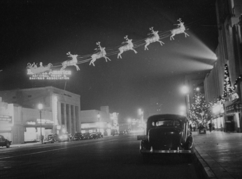 A team of reindeer pulls a loaded sleigh across the sky in this night view of Wilshire Boulevard looking east at Burnside. A neon sign for the Bank of America is visible as well as the El Rey Theater on the far left, and the Wilshire Tower (Desmond's building) on the right. Photogragh circa 1937, (Herman J. Schultheis Collection; Los Angeles Public Library)
