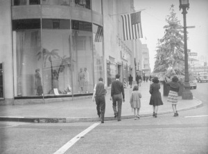 A group of people walks across the street in front of the Desmond's store window. A large Christmas tree with a star on top is on the sidewalk in front of them.  Over the years stores such as Desmond's and Silverwoods have occupied Wilshire Tower's ground floor while professionals have leased offices in the eight-story tower. Located at 5514 Wilshire Boulevard, the Zig-Zag Moderne building was designed by architect Gilbert Stanley Underwood and built in 1928. This building was designated Los Angeles Historic-Cultural Monument #332 in 1987.  Photograph circa 1939. (Herman J. Schultheis Collection; Los Angeles Public Library)
