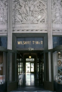 Entrance of the Wilshire Tower, the first Art Deco landmark tower built on Wilshire Boulevard. Over the years stores such as Desmond's and Silverwoods have occupied the ground floor while professionals have leased offices in the eight-story tower. Located at 5514 Wilshire Boulevard, the Zig-Zag Moderne building was designed by architect Gilbert Stanley Underwood and built in 1928.  Photograph dated 1978. (Marlene Laskey Collection; Los Angeles Public Library)