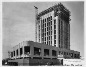 Another view of the Dominguez-Wilshire building under construction.. A sign on the fence identifies the contractor as the C. L. Peck Company. (CSUDH Digital Collections)