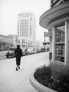 A woman walks past a curved commercial building at the corner of Wilshire Boulevard and Cloverdale Avenue, circa 1937. Across the street is a Myer Siegel Department Store in the Dominguez-Wilshire Building, located at 5410 Wilshire Bouelvard.  The corner of the building at right is the Melody Lane Cafe at Wilshire and Detroit. (Herman J. Schultheis Collection; Los Angeles Public Library)