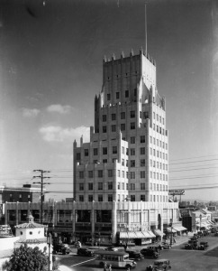 "Traffic at the intersection of La Brea Avenue and Wilshire Boulevard. The E. Clem Wilson Building was built in 1929. Architects: Meyer & Holler. The building was in Art Deco (Zigzag) Moderne style. The Wilson building was used as the exterior of the Daily Planet building in the first season of ""The Adventures of Superman"" television series. Photograph circa 1935. (Security Pacific National Bank Collection; Los Angeles Public Library.)"