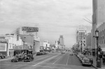 "Looking east along Wilshire Boulevard. The El Rey Theatre is showing a double bill: ""Mr. District Attorney"" (1947) and ""Strange Journey (1946)."