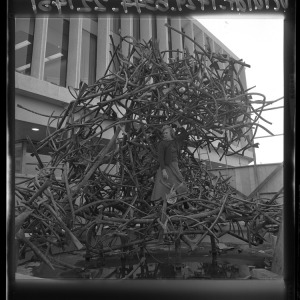 "Artist Claire Falkenstein standing in middle of her ""Sculptured Water"" fountain Los Angeles, Calif., 1965. Falkenstein's sculpture was in front of the California Federal Savings and Loan at 5670 Wilshire Blvd. In the 1990's vandals cut it up and sold the copper for scrap. (Los Angeles Times Photographic Archive. Department of Special Collections, Charles E. Young Research Library, UCLA.)"