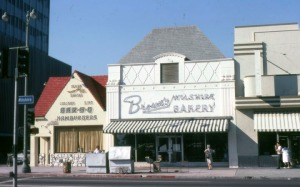 Looking north across Wilshire Boulevard towards three businesses, the Flying Saucer restaurant (left), Brown's Wilshire Bakery (former location of Judy Garland's flower shop), and the Roman Foods Market (right).  In the late 1980s the Flying Saucer – formely Wimpy's –  and Brown's were demolished and a new building was constructed to include the Roman Foods structure as a Staples office supply store. (Marlene Laskey Collection, Los Angeles Public Library)