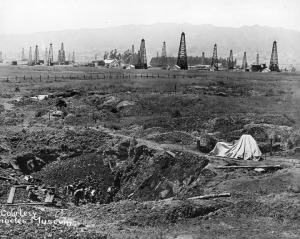 Several men excavate pleistocene animal remains at Rancho La Brea, circa 1911. In the distance is the Hancock Oil fields and the Hollywood Hills. (Security Pacific National Bank Collection; Los Angeles Public Library)
