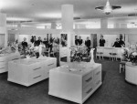 View of the interior of Coulter's Department Store, the ladies undergarments department, with open merchandising spaces punctuated by columns, service areas along the perimeter and horizontal cabinets with rounded corners. Girdles are displayed on the cabinets along with flower bouquets and svelte statuettes. Staff, dressed in black and wearing corsages, pose behind the service counters. Designed by Stiles O. Clements, this classic Streamline Moderne building was first occupied in 1938 by Coulter's Dry Goods. In the 1970s, the store changed hands and became a Broadway. After the building was demolished in 1980, the site remained vacant until the late-2000s, when a 5-story mixed-use structure was built. (Security Pacific National Bank Collection; Los Angeles Public Library.)
