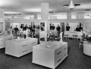 View of the interior of Coulter's Department Store, the ladies undergarments department, with open merchandising spaces punctuated by columns, service areas along the perimeter and horizontal cabinets with rounded corners. Girdles are displayed on the cabinets along with flower bouquets and svelte statuettes. Staff, dressed in black and wearing corsages, pose behind the service counters. Designed by Stiles O. Clements, this classic Streamline Moderne building was first occupied in 1938 by Coulter's Dry Goods. In the 1970s, the store changed hands and became a Broadway. After the building was demolished in 1980, the site remained vacant until the late-2000s, when a 5-story mixed-use structure was built. (Security Pacific National Bank Collection; Los Angeles Public Library)