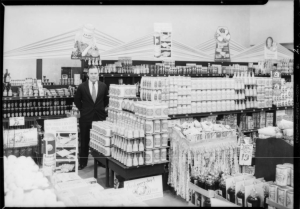 "Photograph of man posing with goods inside Green Spray Market, Southern California, 1932.( ""Dick"" Whittington Photography Collection; USC Digital Library)"
