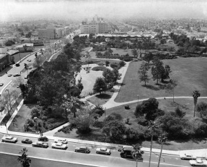 "Panoramic view of the La Brea Tar Pits and the La Break Park on Wilshire Blvd. Spectators lean against the fence as they look at the tar pit. In the background, center, is the May Co. department store. A billboard on Wilshire exhorts viewers to ""Fly Delta."" Photograph dated May 4, 1962. (Herald-Examiner Collection; Los Angeles Public Library)"