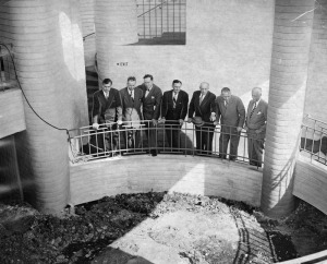 "Officials view a pit at the dedication of the new museum facilities at La Brea. ""At dedication of La Brea Tar Pits. Leaders are shown at civic ceremony marking completion of the first unit of La Brea Pits in Hancock Park. Left to right, Dr. J.H. Breasted jr. of L. A. Museum, Ed Rimpau, president of Miracle Mile Association; Chester W. Stock, chief curator of sciences at museum; A.W. Ross, realtor; Supervisor Roger W. Jessup; Supervisor John Anson Ford; William H. Schuchardt [president of the board of governors of the County Museum]"". Photo dated: Oct. 8, 1949. (Herald-Examiner Collection; Los Angeles Public Library)"