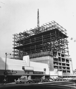 "Lee Tower under construction, 1960.  ""Plenty of work left -- When they finish stackin' stories on Lee Tower, 5455 Wilshire, they'll have 22, at cost of $5,350,000."" -- Examiner clipping attached to verso, dated 14 March 1960. (Los Angeles Examiner Collection, 1920-1961; USC Digital Library)"