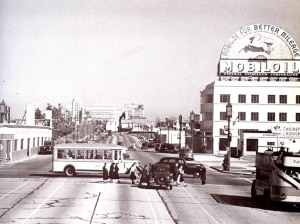 Looking east down Wilshire Boulevard at Fairfax Avenue, 1938. At right is a double-decker bus on the Los Angeles Motor Coach Wilshire line and crossing Wilshire is a bus on the Fairfax Avenue line. The building on the right with the rooftop Mobil Gas billboard is the 6030 Wilshire building (later the location of the A+D Musuem).