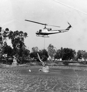 "A helicopter hovers over Howard Ball's sculpture of a wooly mammoth stuck in the La Brea Tar Pits in an attempt to position the sculpture. A rope extends from the helicopter to the mammoth's neck. Other ropes are taut on the surface. The helicopter whips up a circle of waves as it hovers. Photo caption reads: ""A helicopter lowers a statue of a mammoth into the lake at La Brea Tar Pits today"". Photo dated: June 10, 1968. (Herald-Examiner Collection; Los Angeles Public Library)"