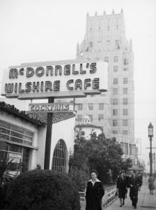 "Exterior view of  McDonnell's Wilshire Cafe on the northwest corner of Wilshire and La Brea. The E. Clem Wilson Building is present in the background. McDonnell's, a local chain of popular drive-ins and restaurants, took possession of the former Dyas-Carleton Cafe around 1931 and opened ""McDonnell's Wilshire Café"". It appears that the restaurant ceased operation at this location sometime after World War II.(Security Pacific National Bank Collection; Los Angeles Public Library)"