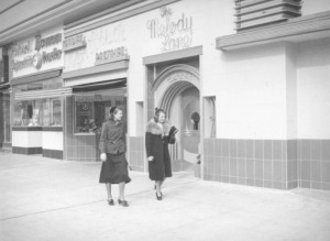 Two women are walking past the Melody Lane Cafe, located on the northwest corner of Wilshire Boulevard and South Detroit Street, circa 1937. The entrance to the restaurant's cocktail lounge features a huge keyhole in the middle of the door. (Herman J. Schultheis Collection; Los Angeles Public Library)