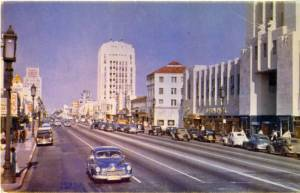 Miracle Mile postcard, circa 1948. Looking east down Wilshire from Burnside Avenue featuring the El Rey Theatre and E. Clem Wilson Building  on the north (left) side of the street and Desmonds Department Store and Wilshire-Dominguez building on the south side. Kodachrome postard, circa 1948. (CSUDH Digital Collections)