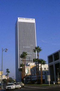 "Looking southeast down Wilshire Boulevard towards the Mutual Benefit Life Plaza; a few storefronts are seen directly west of the office complex. Located at 5900 Wilshire Boulevard and completed in 1971, the plaza includes a 32-story office building and two smaller buildings designed by William L. Pereira. The building served as the headquarters for Mutual Benefit Life until their bankruptcy in 1991. It was later known as the ""Variety"" building and is now know as the ""SBE"" building. (Marlene Laskey Collection; Los Angeles Public Library)"