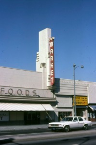 Looking northeast across Wilshire Boulevard towards two commercial buildings; the storefront on the right, located at 5403 Wilshire Boulevard, is shown when it was occupied by a copy center. Roman Foods Market (left), located at 5407 Wilshire Boulevard, later became a Staples office supply store.  (Marlene Laskey Collection; Los Angeles Public Library)