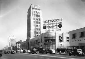 "A view of Silverwood's in the Wilshire Tower (better known as the Desmond's building). A large sign on top of the store displays ""Silverwoods, Hart Schaffner & Marx, clothes"". The corner of the building is curved and has a large expanse of glass that covers two stories. A 20 mph speed limit sign is posted on a street light. Photograph dated: Jun. 24, 1936. (Los Angeles Public Library.)"