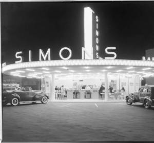 Simon's Drive-In Cafe, circa 1939. Located at the intersection of Wilshire and Fairfax, the restaurant was distinguished by the tall pylon emerging from the center of the round building. It was built in 1935 and designed by  architect Wayne McAllister, who designed many drive-in restaurants. (Dick Whittington Studio, Huntington Digital Library.)