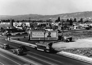 "Simon's Drive In Cafe at the northwest corner of Fairfax and Wilshire; photograph dated 1938. The following year construction would begin on the May Company on the lot with the billboard. In 2014 work is scheduled to begin converting the former May Company building into the Academy Museum. (""Dick"" Whittington Photography Collection, 1924-1987; USC Digital Collection)"