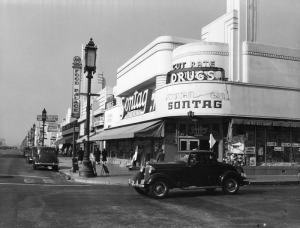 View looking west at the intersection of Wilshire Boulevard and Cloverdale Avenue, circa 1939. The Sontag Drug Store is seen on the northwest corner. Today it is the location of Wilshire Beauty Supply. A sign for the A and P Food Palace can be seen, the grocery store was next-door to Sontag's.