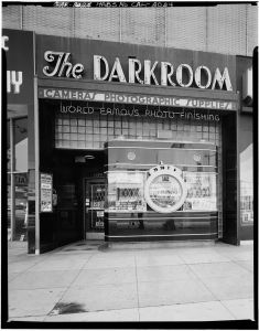 "The Darkroom was a Miracle Mile camera store located at 5370 Wilshire Boulevard. The original building was constructed in 1926, but the ""camera"" storefront was built in 1938. It was designed by architect Marus Miller. It's black vitrolite glass façade is one of the most famous examples of roadside or programmatic architecture in the world – and one of the last remaining examples in Los Angeles. Its design has been replicated at Disney Studios Paris and Universal Studios Orlando. The store is now part of El Toro Cantina. The façade is protected as a Los Angeles Historic-Cultural Monument. [Photo courtesy of the Library of Congress; Marvin Rand, photographer.]"