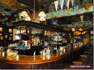 "Contemporary view of the horseshoe-shaped bar at Tom Bergin's tavern. The establishment is decorated with cardboard shamrocks bearing the names of ""regular""customers, including Cary Grant and Kiefer Sutherland.(Photograph courtesy of iamnotastalker.com)"