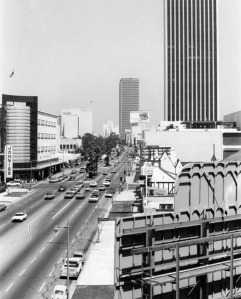 View is looking east from Fairfax towards the Miracle Mile section of Wilshire Boulevard, 1972. First building on the left is the May Co. building, designed by architect A.C. Martin, and built in 1939. Second building is the Los Angeles Museum of Art, designed by architects: Pereira & Assoc., and built in 1964. Third building is the Prudential Building (later Museum Square), designed by Wurdeman & Becket, and built in 1948. The California Federal Plaza Building is the tall building in the right background; in the right foreground is the Mutual Benefit Building at 5900 Wilshire Boulevard.  (Los Angeles Public Library)