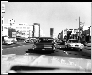 A view of Wilshire Boulevard from a car showing the May Company building, April 28, 1964. The street is lined with an assortment of buildings, including the four-story May Company at left. The California Federal Bank building can be seen under construction in the