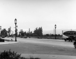 A view of Wilshire Boulevard looking west across Masselin Avenue. Notice the ornate lamp posts on each side of the street. The billboard on the right encourages businesses to locate in the Miracle Mile.  (Los Angeles Public Library)