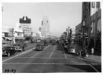 Looking east along Wilshire Boulevard with the E. Clem Wilson Building at La Brea and Wilshire in the background. The Dominguez-Wilshire building is on the right. Sontag Drug Store is on the left. Photograph circa 1940. (USC Digital Library)