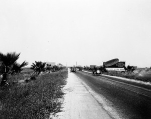 Cars travel in both directions on Wilshire Boulevard, as seen from east of La Brea Avenue. Small palm trees and billboards are seen on both sides of the boulevard. Photograph dated 1920. (Blackstock Negative Collection ; Los Angeles Public Library)