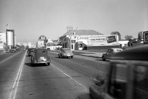 Looking southeast down Wilshire Boulevard at San Diego Way (right, out of view). Various businesses, including the May Co. store at Wilshire and Fairfax (left), are seen on both sides of the boulevard; storefronts are being added onto the Carthay Building (center). The Foster and Kleiser billboard right of center is advertising Farmers and Merchants National Bank of Los Angeles. Photograph dated April 4, 1947. (Los Angeles Public Library)