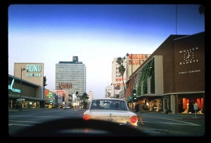 Windshield view from a car driving east along Wilshire Boulevard, circa 1963. The Muellen and Bluett store on the right is decorated for the Christmas holiday. On the left is the Bond Clothing store. The white vehicle is a 1963 Ford Falcon.