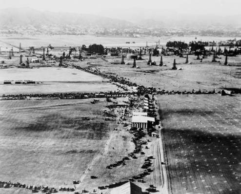 Aerial view, circa 1920, looking north along Fairfax Avenue at the intersection of Wilshire Boulevard. An aviation fair in underway at Chaplin Airfield. DeMille Airfield in located in the upper left corner. (Water and Power Associates.)