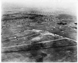 Photograph of an aerial view of the intersection of Wilshire Boulevard and Fairfax Avenue, showing Rogers Airport, Los Angeles, 1920. The towers of oil siphons fill the expanse of cleared land above the intersection of the two roads. A few striped display tents have been pitched in the clearing below them. There is a possibility that the road on the lower right corner is what eventually became Olympic. The diagonal dirt road above it is what became San Vicente blvd. The road that goes from left to right midway up the photo is Wilshire, and the one that intersects it Fairfax, which at that time may still have been called Crescent Avenue. (Caption and photograph courtesy of USC Digital Library.)